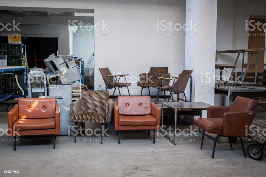 Vintage leather armchairs from the 70's for sale in the warehouse of an antique dealier in a flea market stock photo