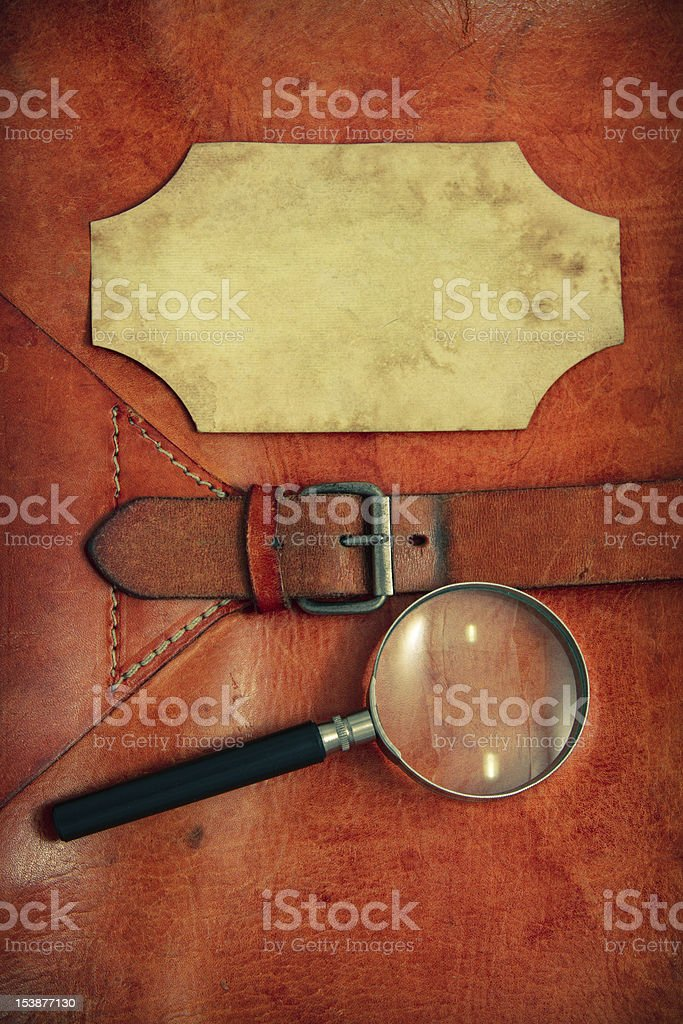 Vintage leather background with paper frame and magnifying glass royalty-free stock photo