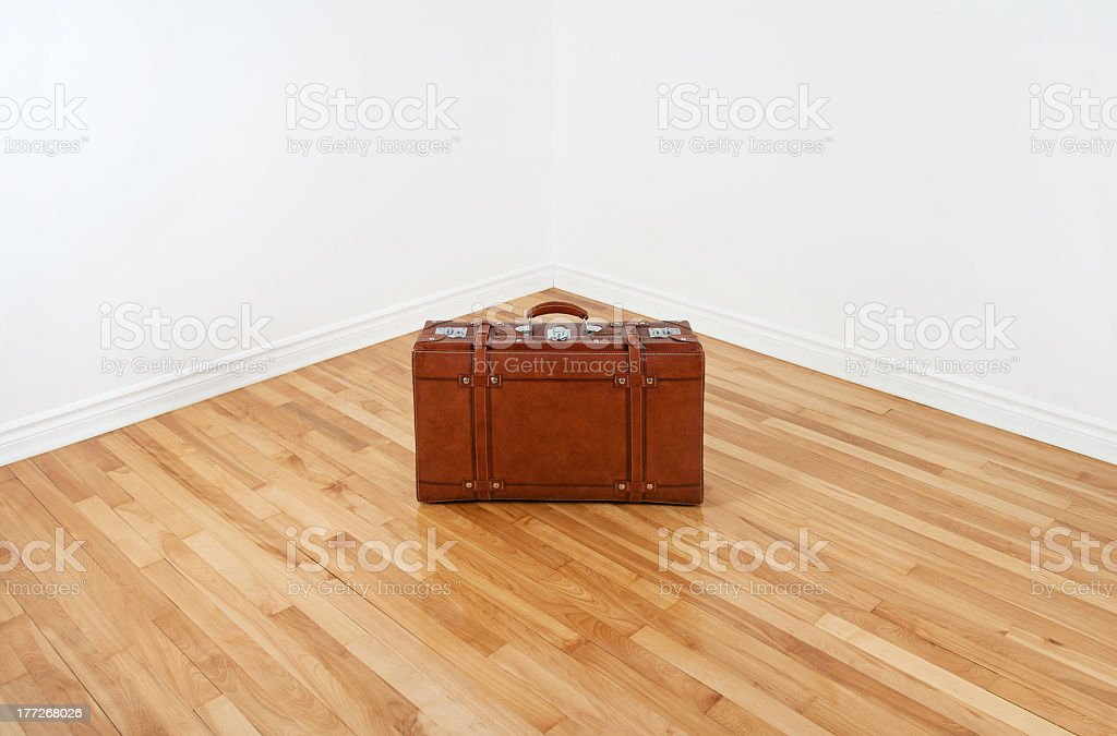 Vintage leather suitcase in empty room corner royalty-free stock photo