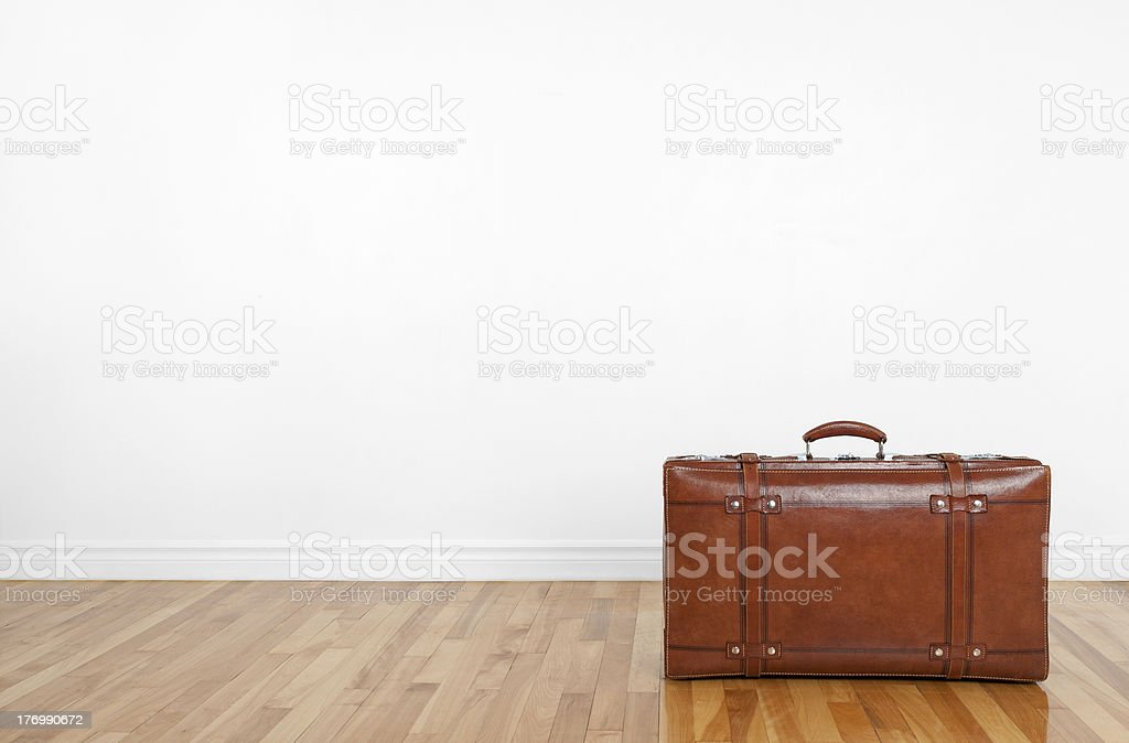 Vintage leather suitcase on a wooden floor royalty-free stock photo