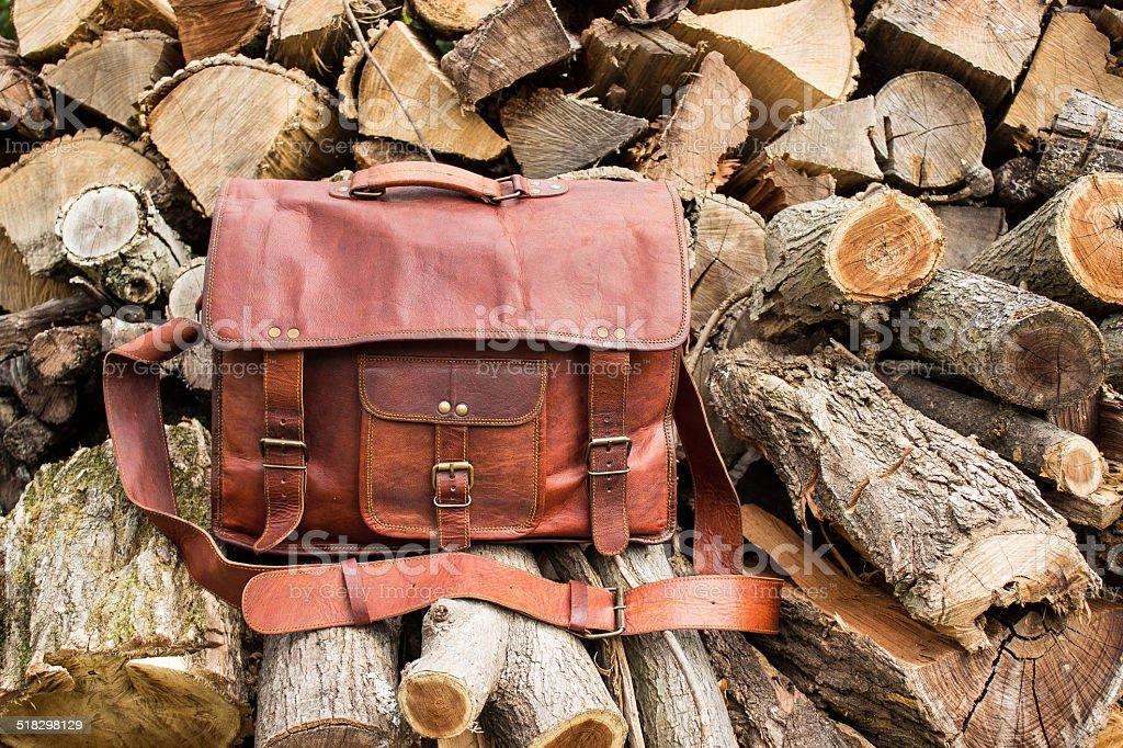 Vintage look handmade leather messenger bag wood pile stock photo