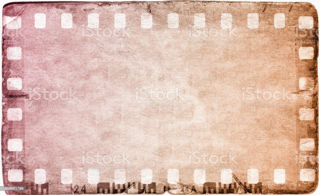 Vintage magenta film strip frame on old and damaged paper background. stock photo