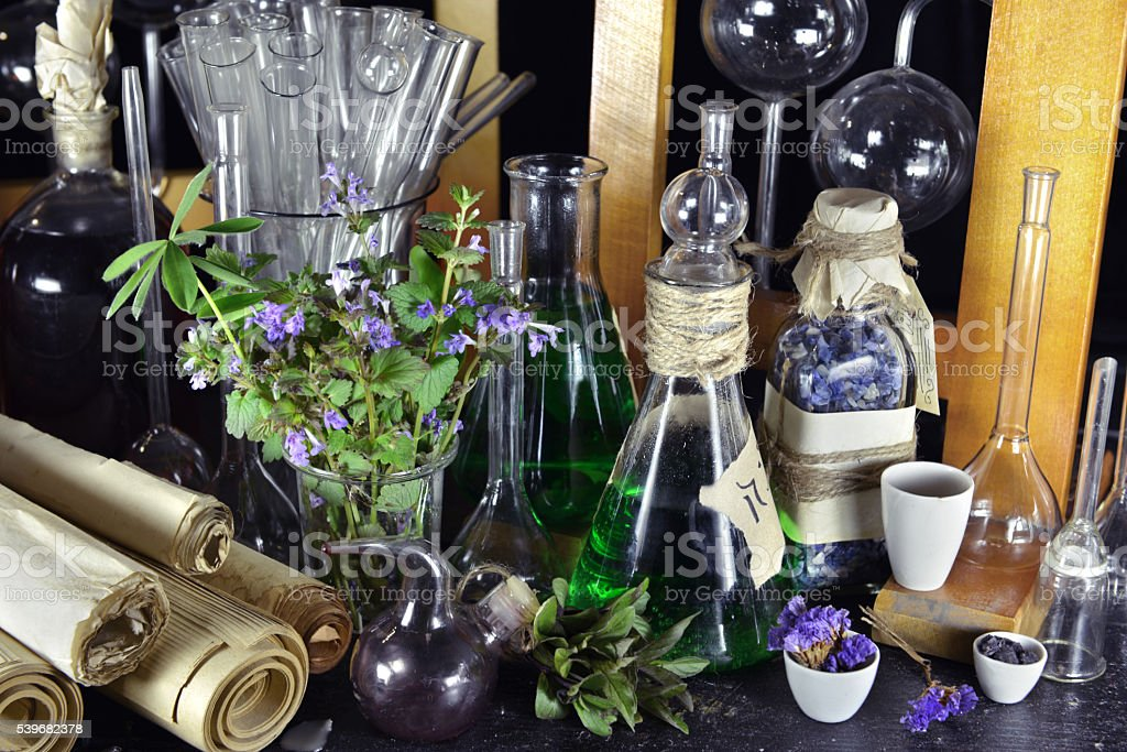 Vintage magic bottles, scrolls and lilac flowers on witch table stock photo