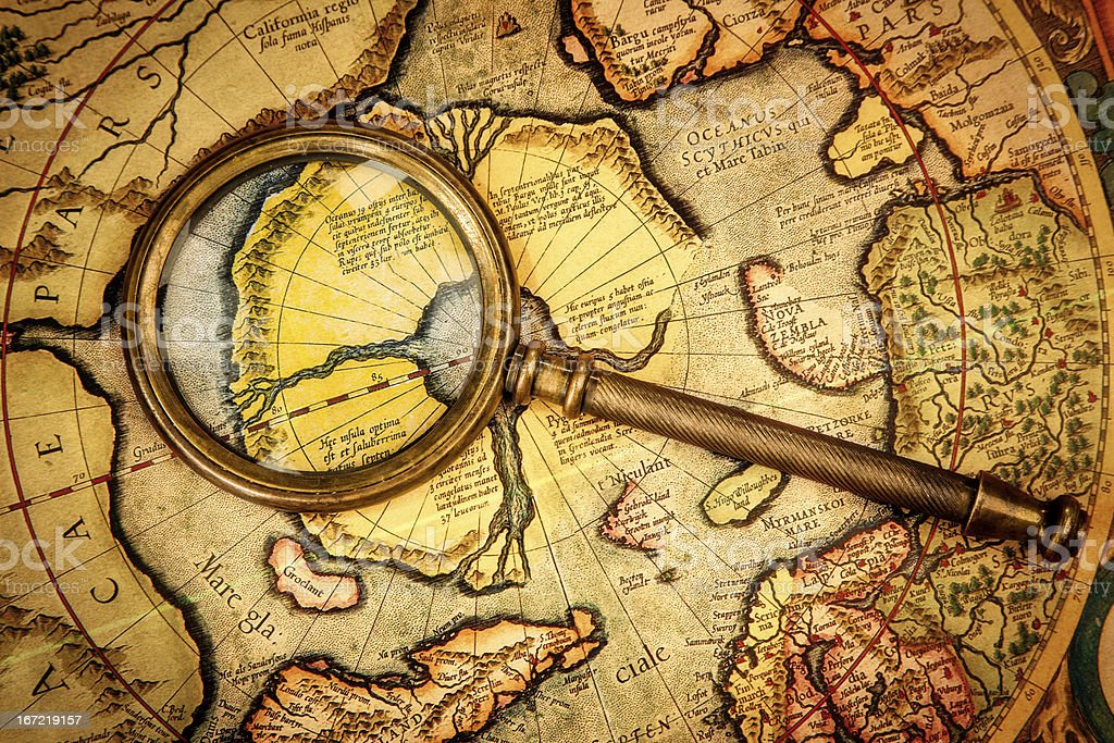 Vintage magnifying glass lies on the ancient map North Pole. royalty-free stock photo
