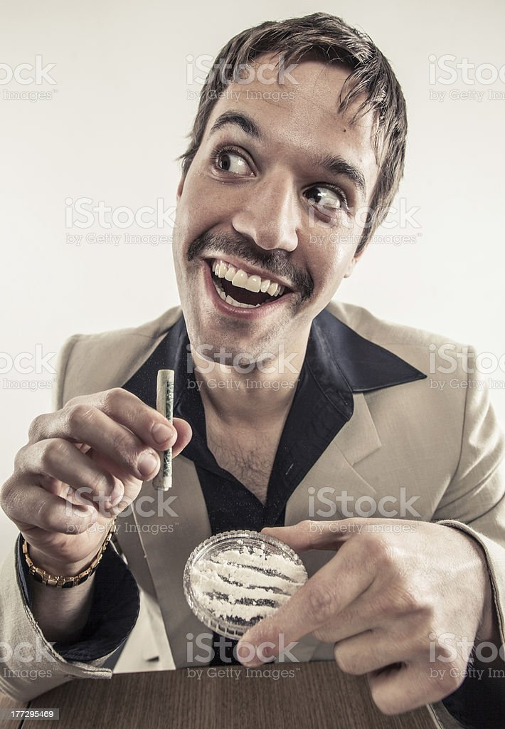 Vintage man with mustache and suit doing cocaine at table stock photo