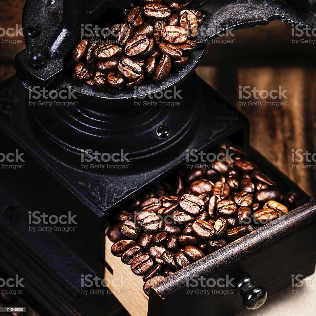 Vintage manual coffee grinder with cofee beans on wooden stock photo