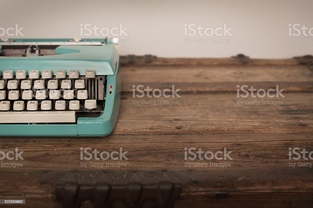 Vintage Manual Typewriter on Wood Trunk, Teal stock photo