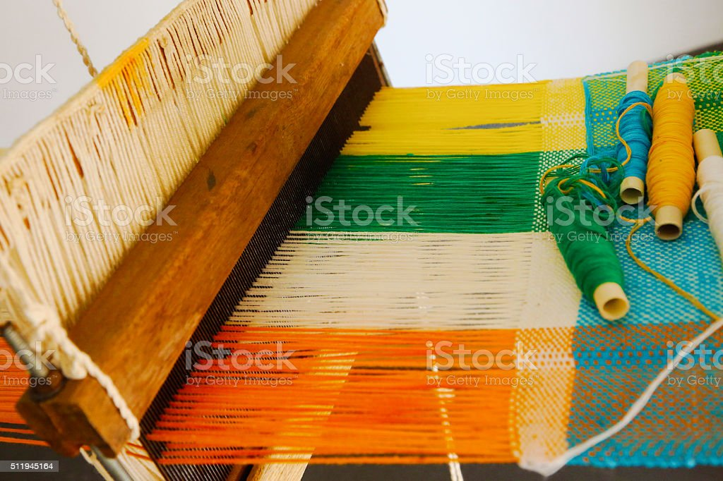 Vintage manual weaving loom with unfinished textile work stock photo