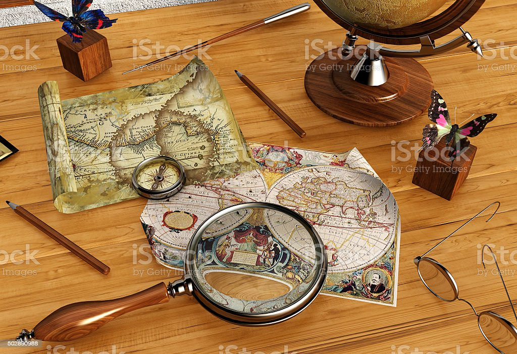 Vintage maps and magnifying glass on wood table stock photo