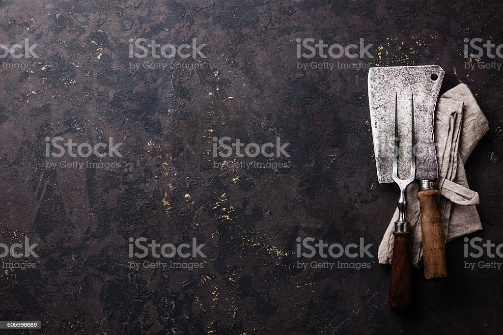 Vintage Meat Fork and Cleaver on dark background stock photo