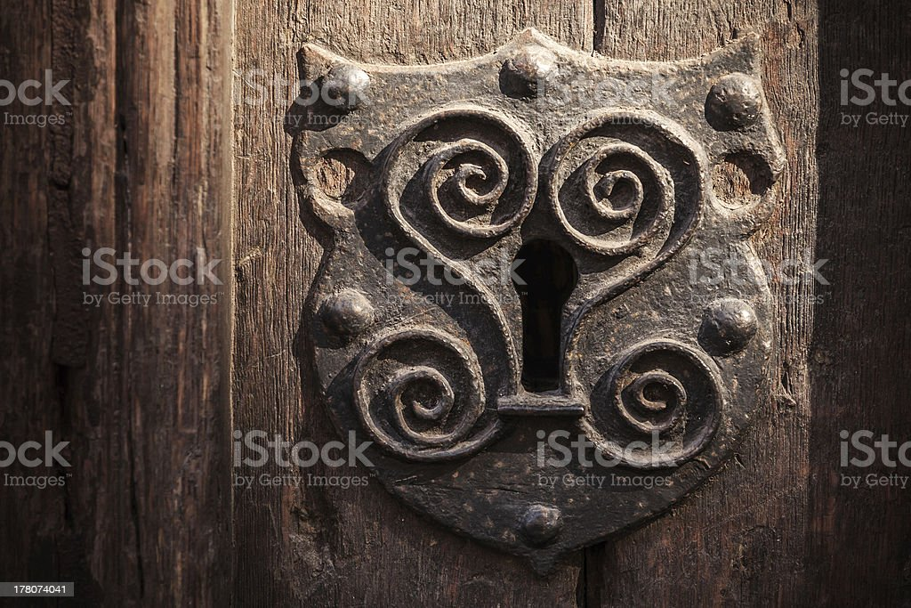 Vintage metal keyhole decorative element on weathered wooden surface royalty-free stock photo