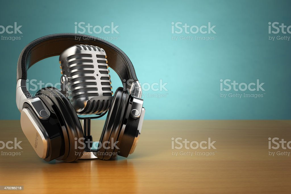 Vintage microphone and headphones on green background. stock photo
