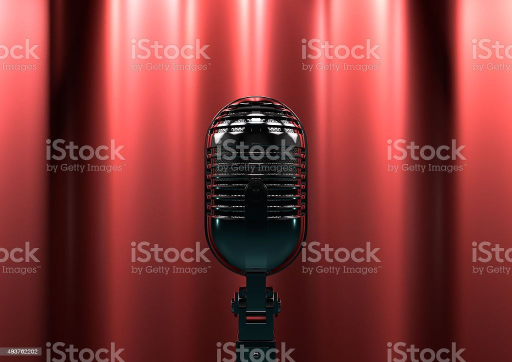 Vintage microphone on stage with red curtains. Moody stage light stock photo