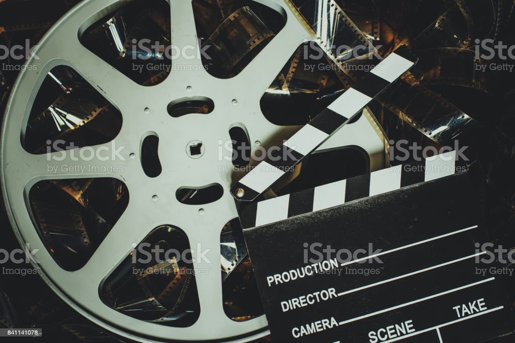 Vintage movie background, reel filmstrip and clapper board stock photo