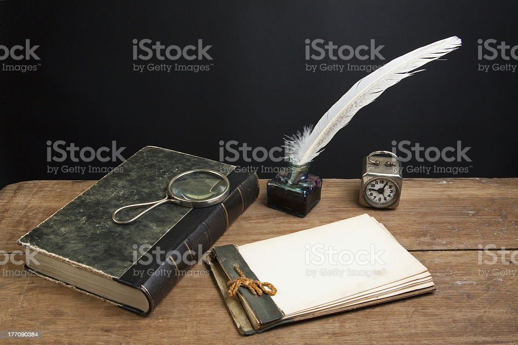 Vintage notepad, book, quill pen and inkwell, magnifying glass, clock royalty-free stock photo