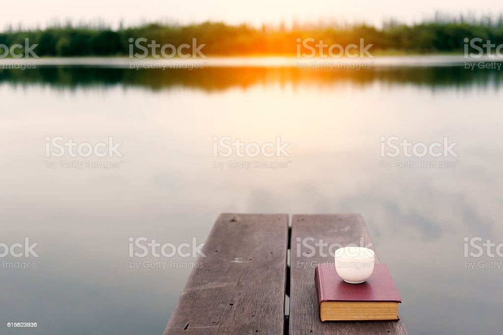 Vintage old book with coffee cup on wood balcony by stock photo