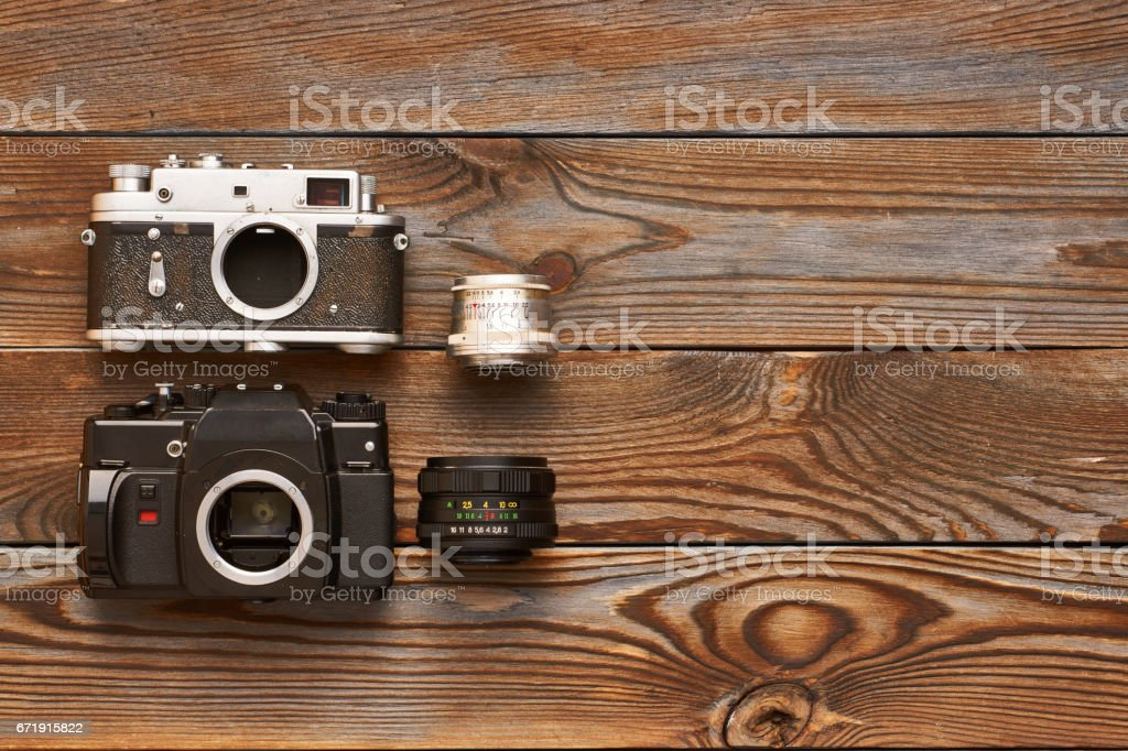 Vintage old cameras and lenses on wooden background stock photo