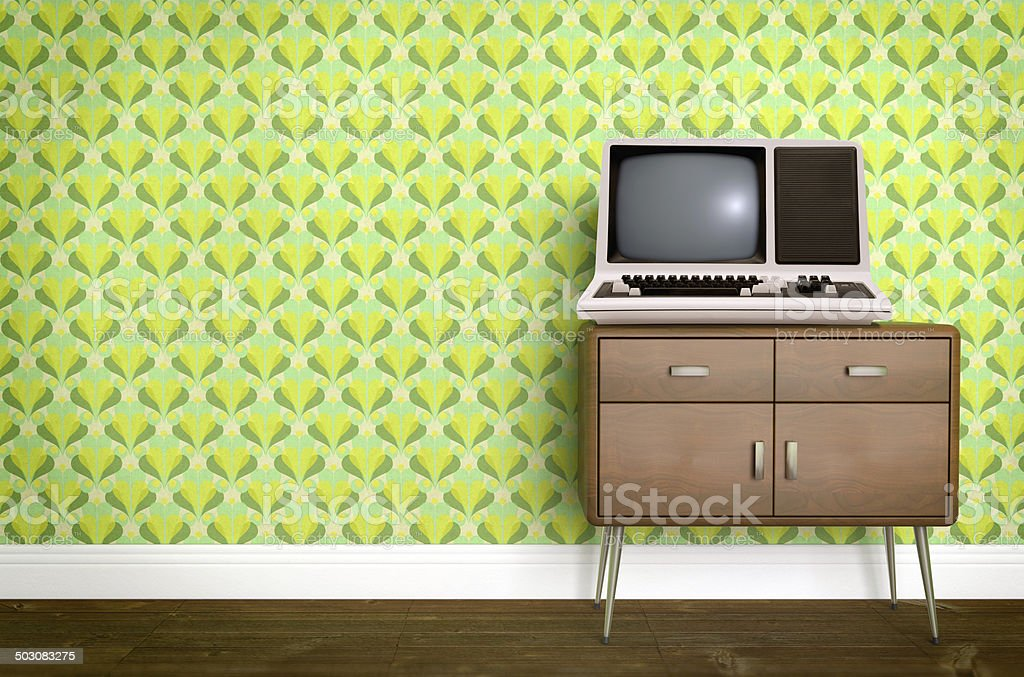 Vintage old computer on sixties, seventies wallpaper and furniture stock photo