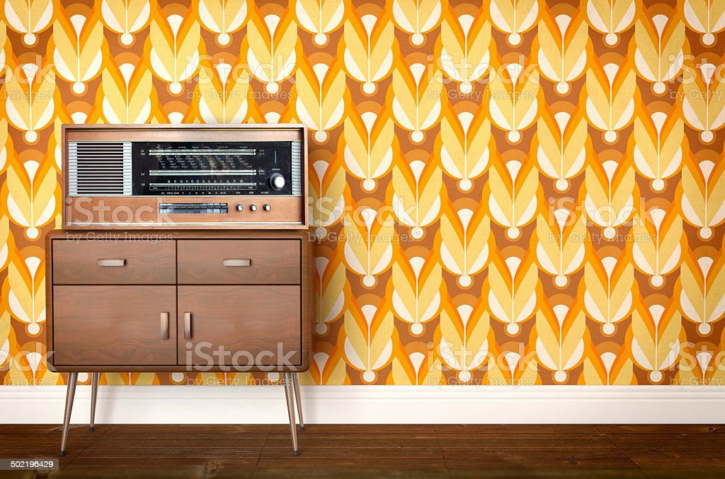 Vintage old radio on sixties, seventies wallpaper and furniture stock photo
