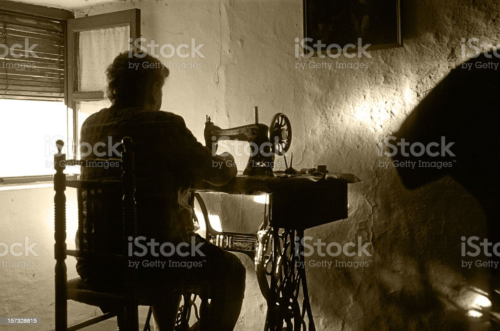 vintage: old woman with sewing machine royalty-free stock photo