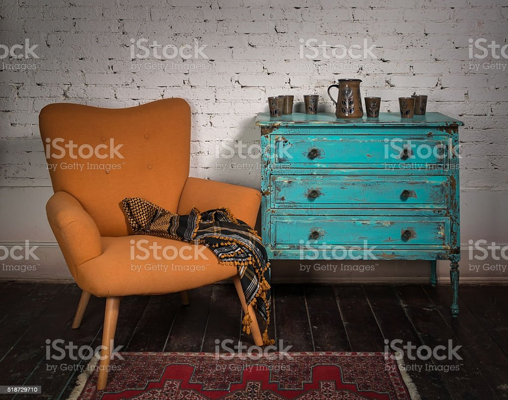 Vintage orange armchair, blue cabinet and ornate scarf stock photo