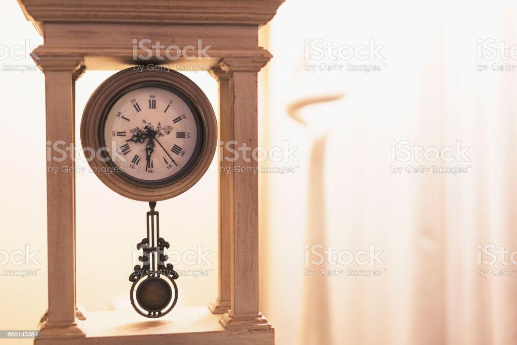 Vintage Pendulum Clock near a brightly lit floor lamp stock photo