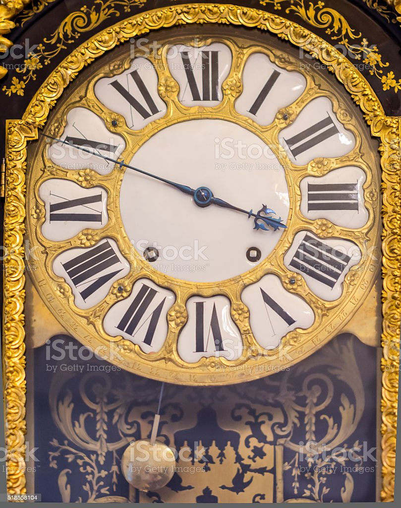Vintage pendulum clock with gilded pattern stock photo
