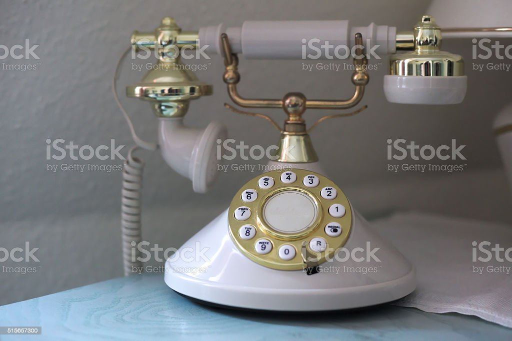 Vintage phone with a golden dial plate stock photo