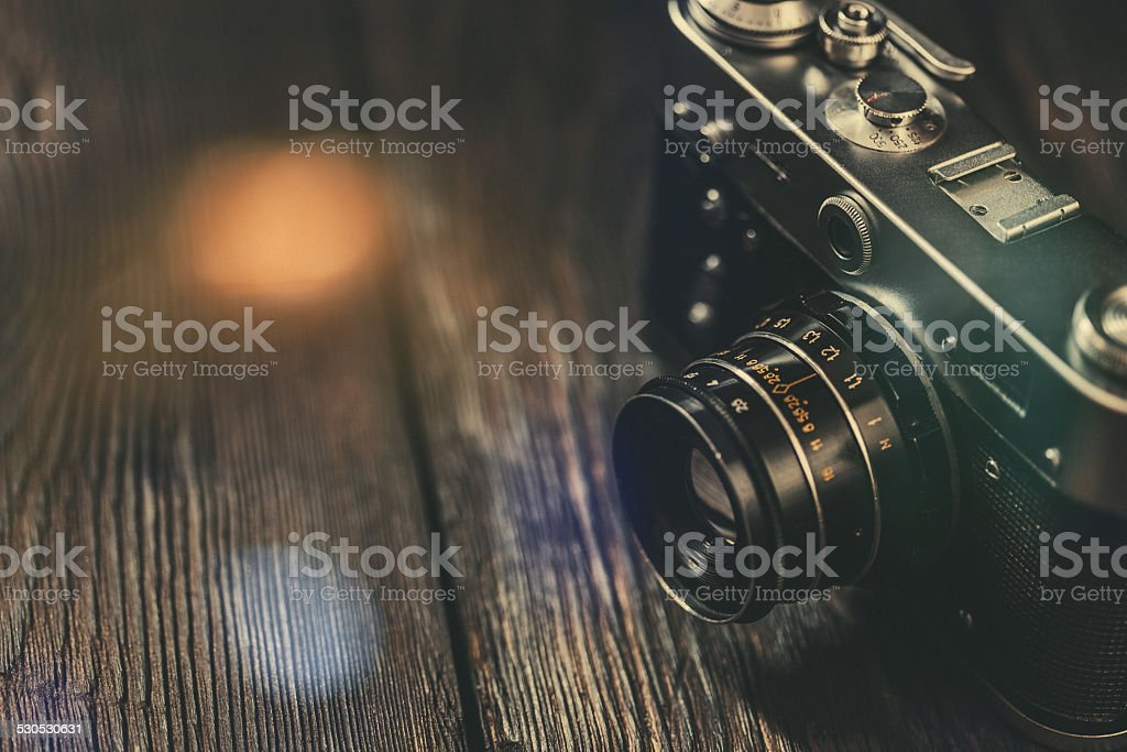 Vintage photo camera on old wooden table stock photo