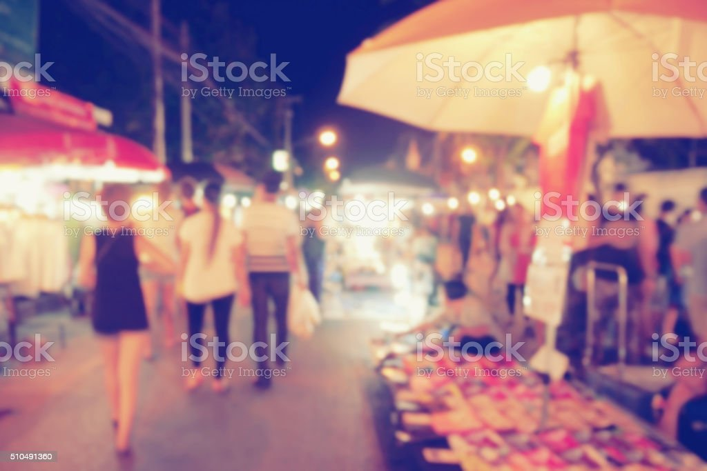 vintage photo effect of blurred people walking at night market stock photo