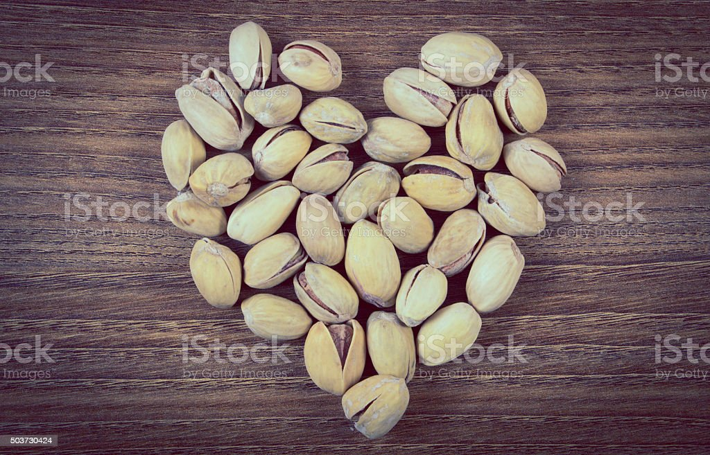 Vintage photo, Heart of pistachio nuts on wooden table stock photo
