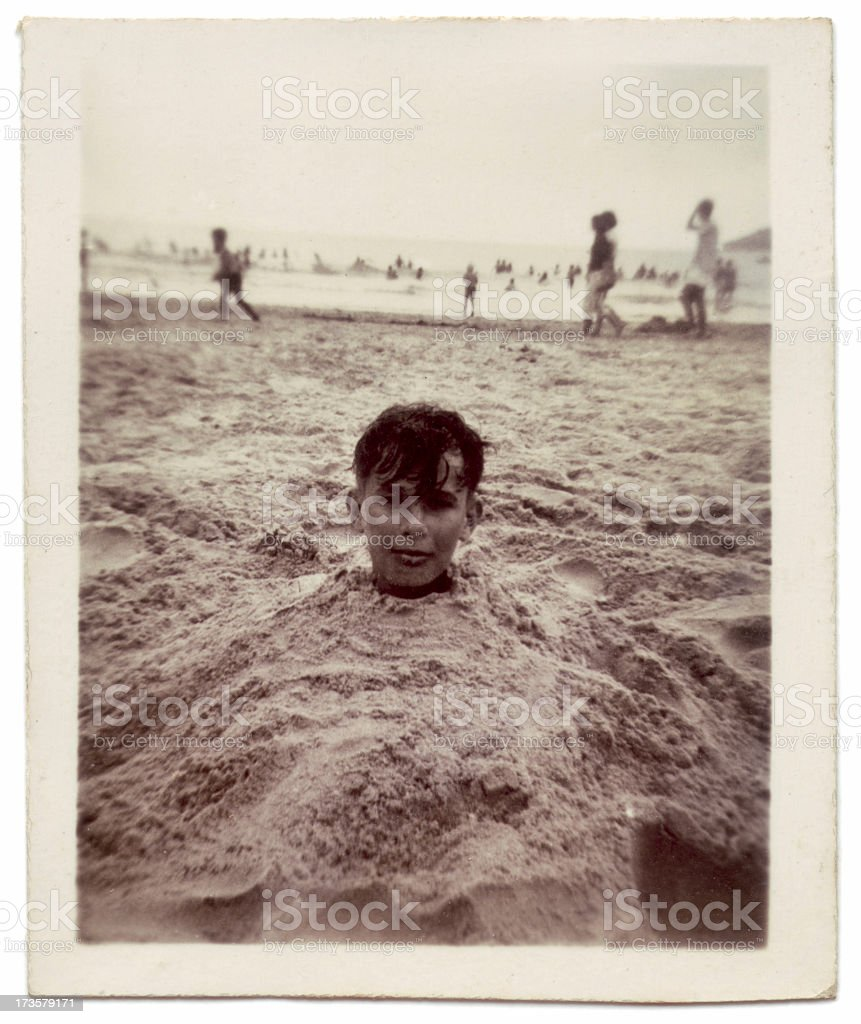 Vintage photo of boy buried in sand at the beach stock photo