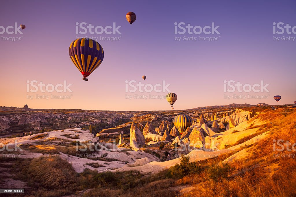 Vintage photo of hot air balloon flying over rock landscape stock photo