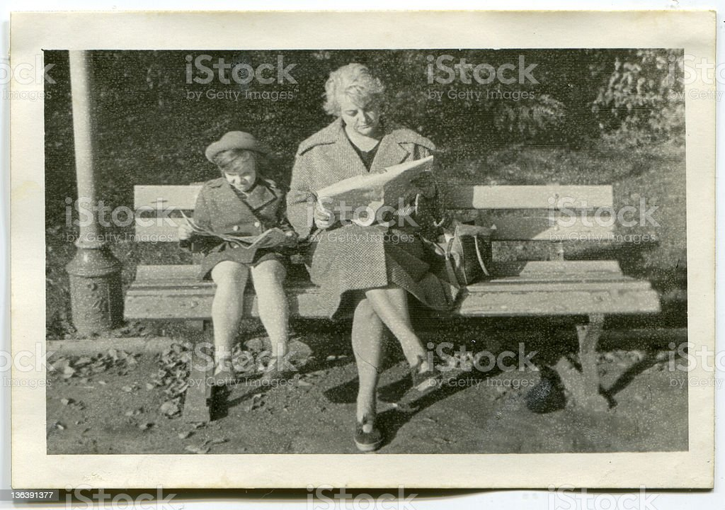 Vintage photo of mother and daughter reading in park stock photo
