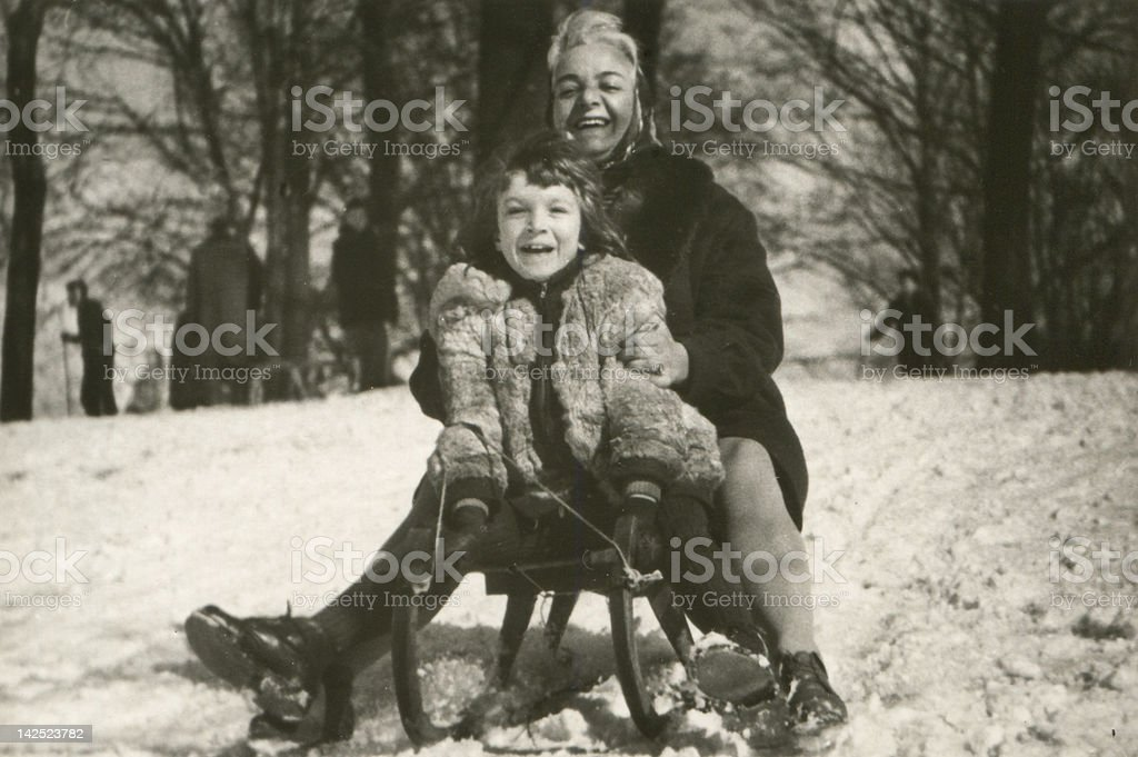 Vintage photo of mother and daughter sledding stock photo