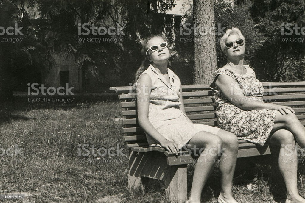 Vintage photo of mother and daughter sunbathing stock photo