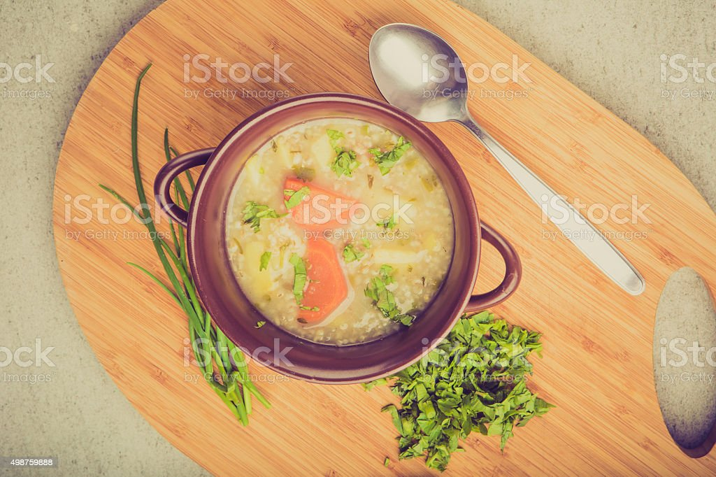 Vintage photo of traditional barley soup with parsley in bowl stock photo