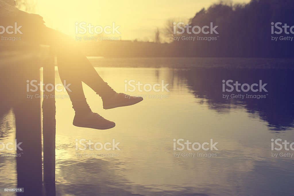 Vintage photo of woman relaxing at the lake in sunset stock photo