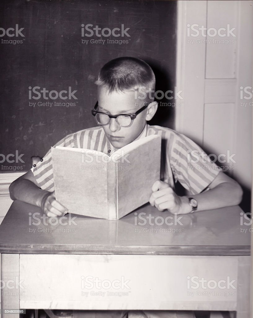 Vintage Photo of Young Boy Reading Book stock photo