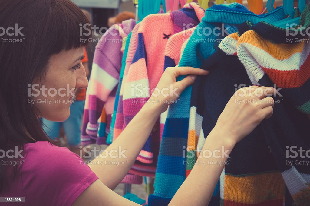 Vintage photo, Woman shopping clothes on stall at the bazaar stock photo