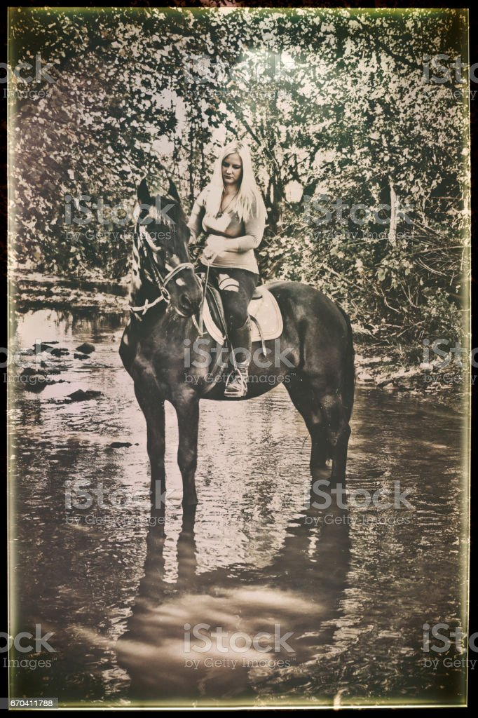 Vintage photograph of a Young Woman Riding Horse Across River stock photo