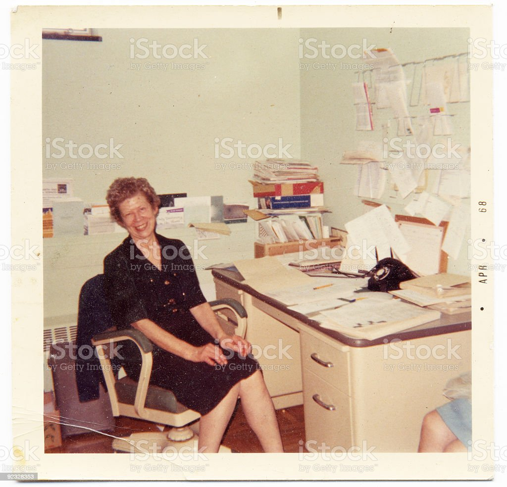 Vintage photograph of an happy secretary sitting at her desk stock photo