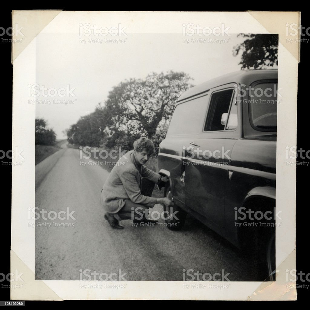 Vintage Photograph of Man Checking Rear Tire on Truck stock photo
