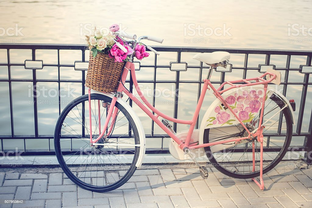 Vintage pink bicycle with flower basket stock photo