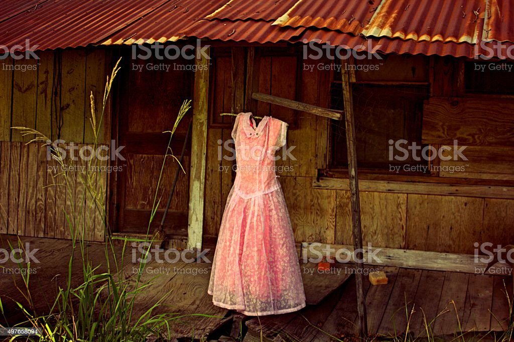 Vintage Pink Party Dress on Porch of Abandoned House stock photo