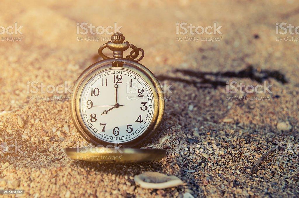 vintage pocket watch on sand beach background stock photo