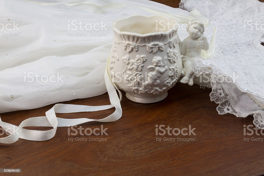 Vintage porcelain christening cup and baptism dress on wood stock photo