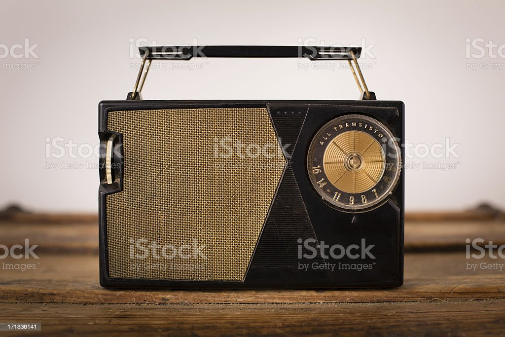 Vintage, Portable Gold and Black Radio Sitting on Wood Table royalty-free stock photo