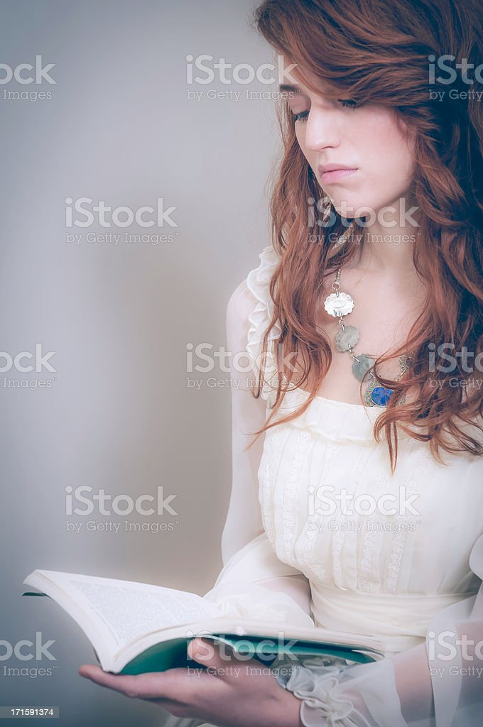 Vintage portrait of a young woman reading her book stock photo