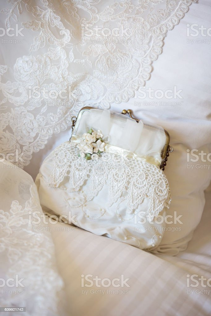 Vintage Purse Displayed On Bed with Wedding Dress stock photo